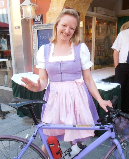 Austria woman in costume waving and standing by bike