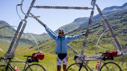 Biker posing with giant bicycle sculpture on French Alps to French Riviera tour