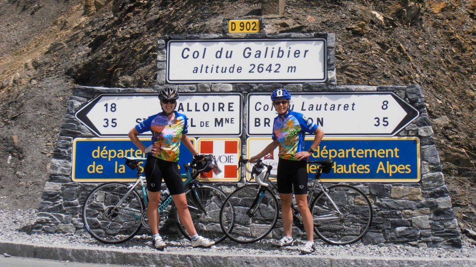 Bikers posing by sign on the French Alps to French Riviera tour