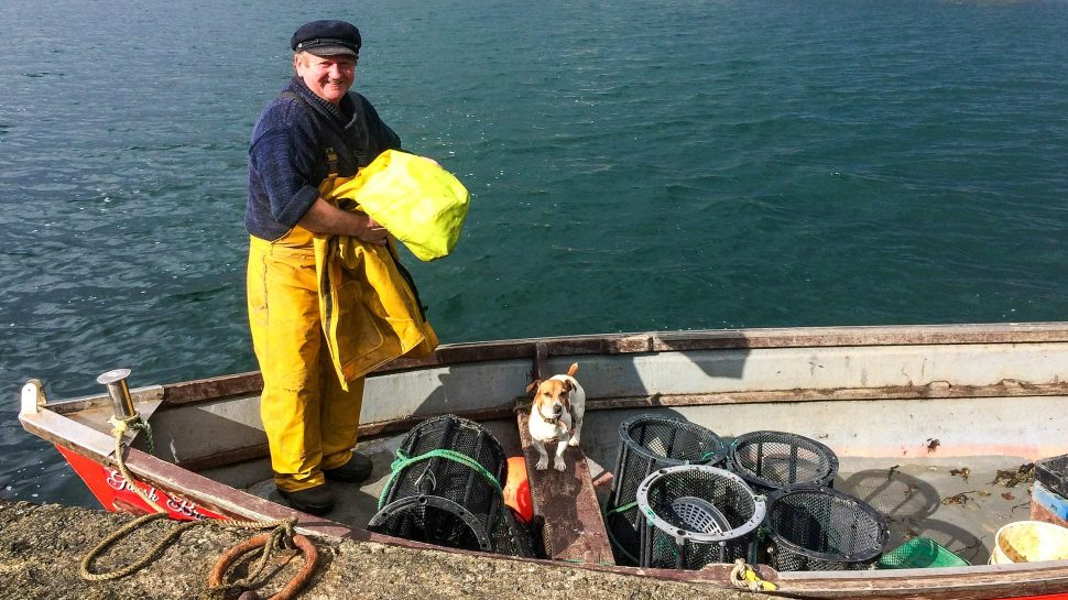 Irish fisherman in boat with dog