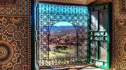 Mosaics and metal scrollwork window in Morocco