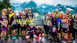 Bikers posing from platform overlooking mountainside castle on Munich to Verona tour