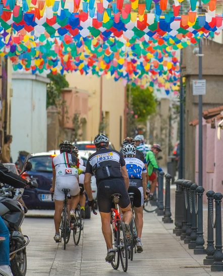 Biking through a street with balloons in Savor Sardinia