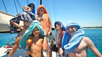 Kids on a sailboat relaxing in the Sardinian sun