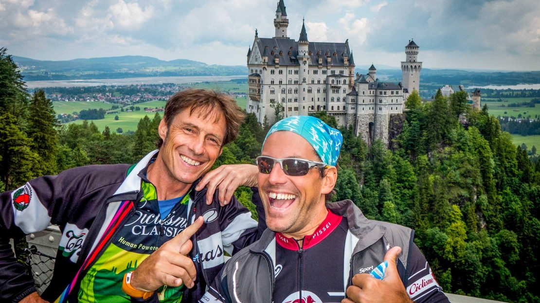 Two bikers on the Munich to Verona tour posing near a castle