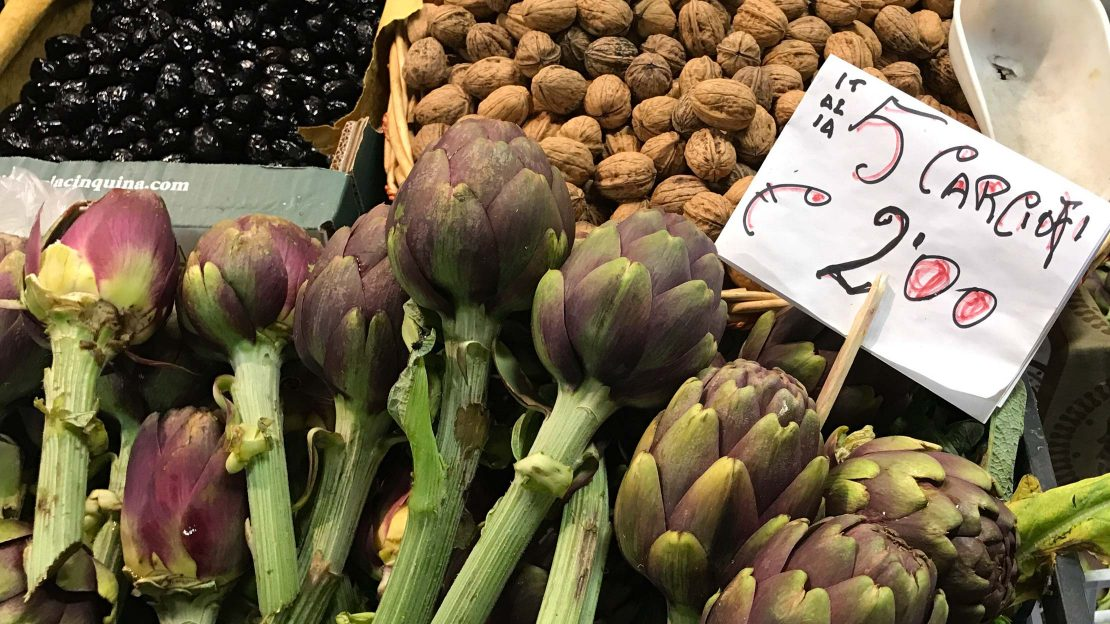 Artichokes, nuts, and olives at a food market
