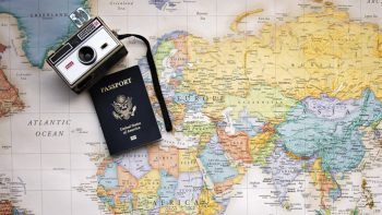 Camera and passport on top of a map