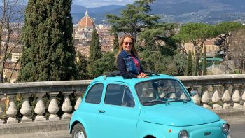 Lauren in a blue Fiat with Florence in the background